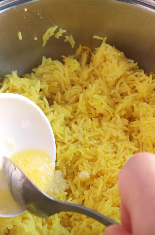 Añadiendo Mantequilla preparando Arroz Amarillo aromático