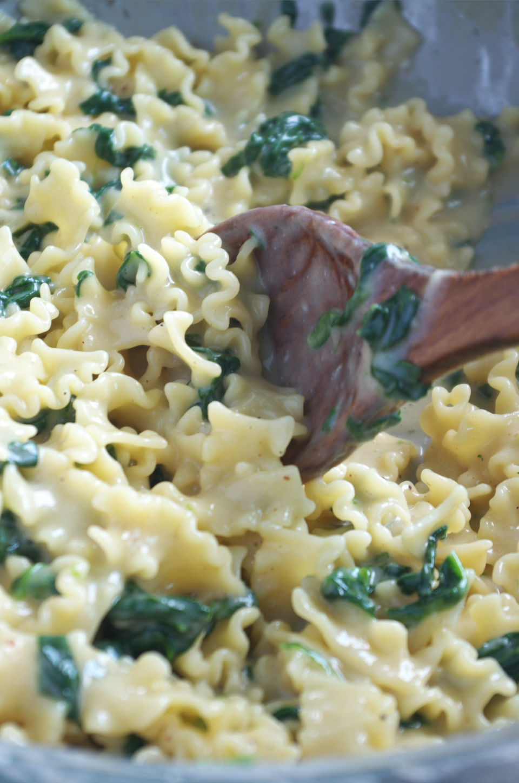 Removiendo con cuchara de palo la sartén con la pasta tipo mafalda corta con espinacas y jamón
