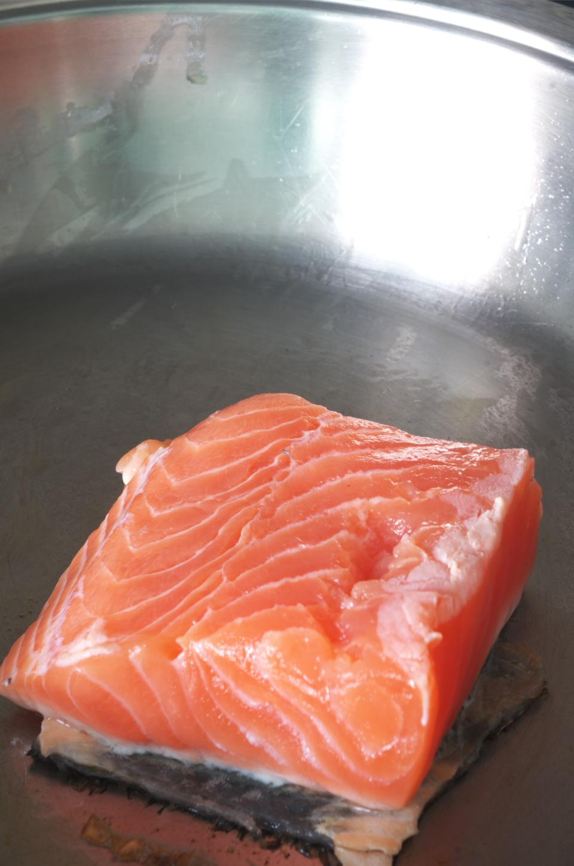 Cocinando salmón y su piel debajo para receta de Primer plano de salmón con salsa de arroz integral en plato