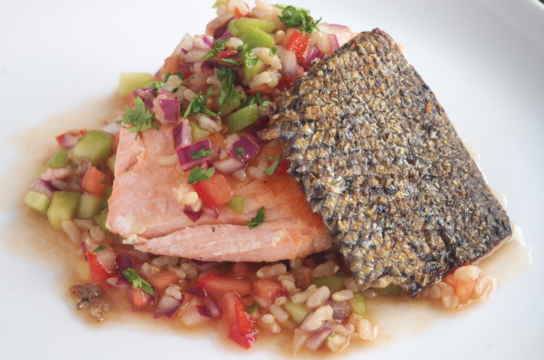 Primer plano de salmón con salsa de arroz integral en plato