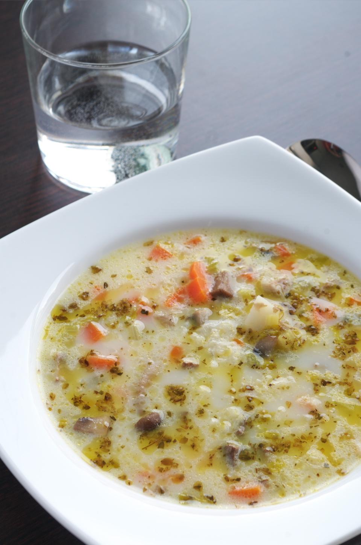Sopa de arroz, setas y verduras en plato junto con vaso y cuchara