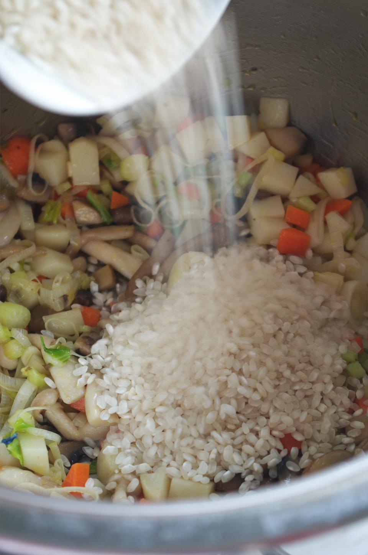 Añadiendo arroz en receta de sopa de arroz, setas y verduras