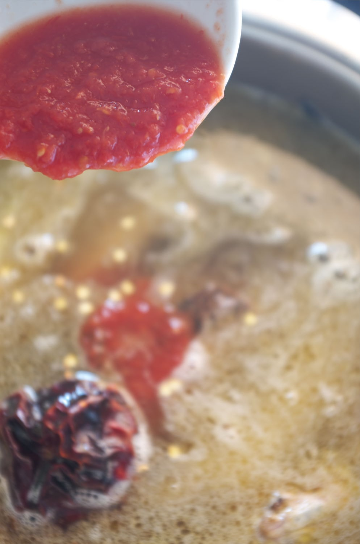 Añadiendo tomate a fumet de pescado
