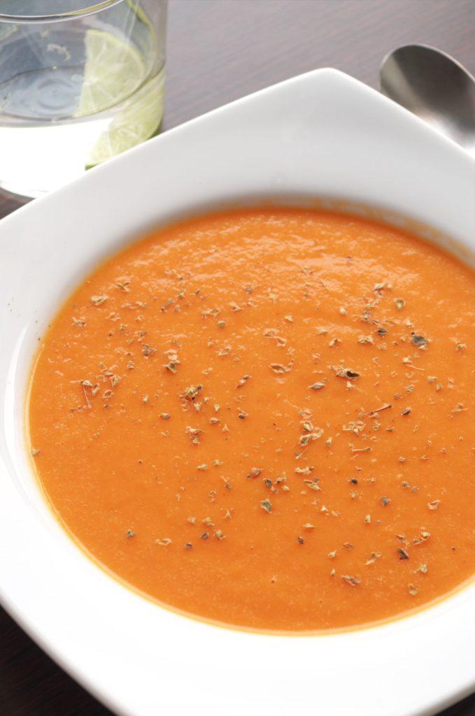 Plato resultado de preparar la receta de Sopa de tomate asado decorado con orégano